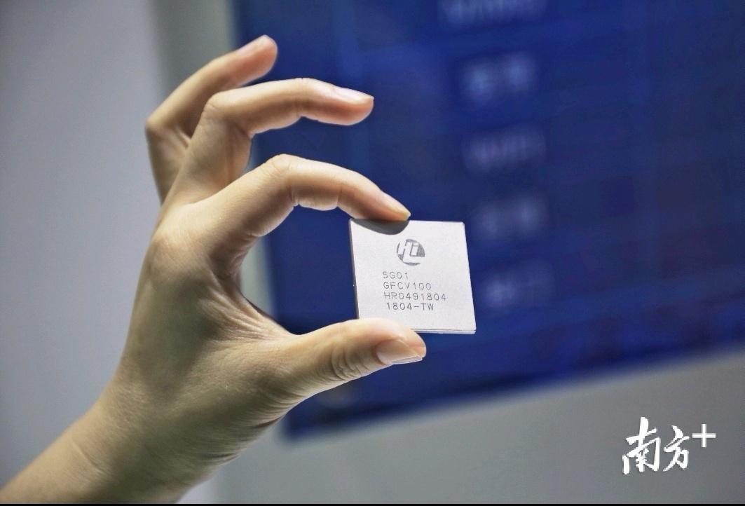 工作人员正在展示华为5G通信芯片。
