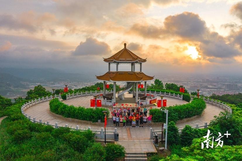 7月1日早上,阳江市金鸡岭公园的最高点上,市民挥舞着旗帜为伟大的中国共产党祝福。刘正亮 摄