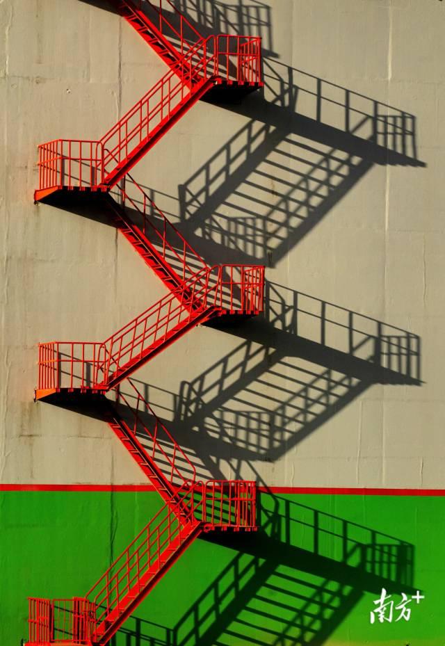 10月6日,广州番禺,一缕朝阳照在红色折梯上,投影绘制出一幅几何之美。shipio 摄
