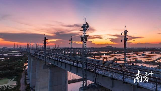 10月3日傍晚,广州南沙港铁路即将通车,电力工人在夕阳余晖中架设电路。黎明朗 摄