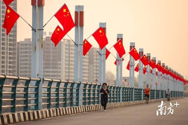 10月1日早上,阳江鸳鸯湖环湖路上五星红旗迎风飘扬,市民在晨光下锻炼。刘正亮 摄
